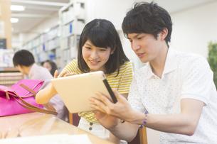 スマートデバイスを操作する学生男女の写真素材 [FYI02972693]