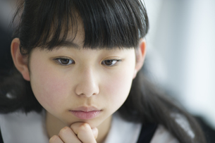 教室で考え事をする女子学生の写真素材 [FYI02972695]