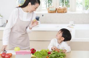 キッチンで笑い合う母と男の子の写真素材 [FYI02972705]