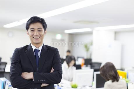オフィスで腕組みをして笑うビジネス男性の写真素材 [FYI02972711]