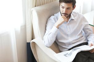 ソファーに座って考え込む男性の写真素材 [FYI02972714]