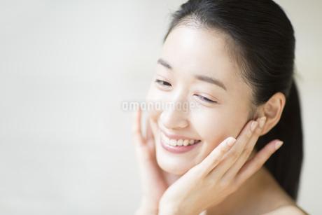 頬に両手を添えて微笑む女性の写真素材 [FYI02972715]