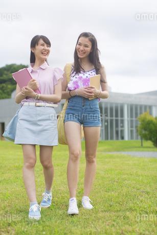 笑いながら芝を歩く2人の女子学生の写真素材 [FYI02972716]