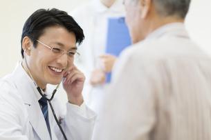 患者に聴診器をあてる男性医師の写真素材 [FYI02972717]