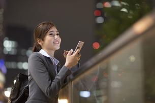 夜の街を背景にスマートフォンを持ち遠くを眺めるビジネス女性の写真素材 [FYI02972719]