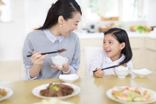食事中に顔を見合わせて笑う母と娘の写真素材 [FYI02972721]