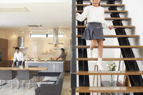 階段を駆け降りる女の子とダイニングにいる夫婦の写真素材 [FYI02972722]