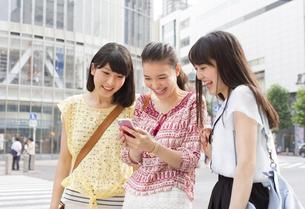 スマートフォンを見つめて喜ぶ3人の若い女性の写真素材 [FYI02972735]