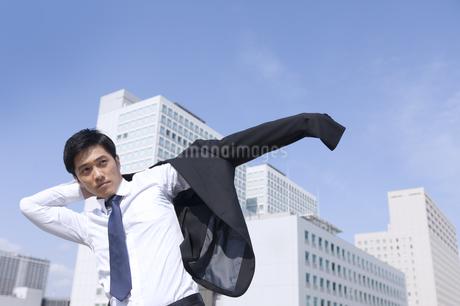 ビルを背景にジャケットに袖を通すビジネス男性の写真素材 [FYI02972748]