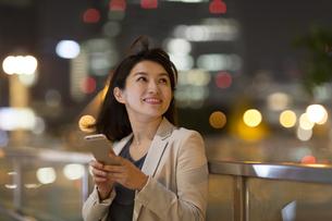 夜の街を背景にスマートフォンを持ち上を見上げるビジネス女性の写真素材 [FYI02972762]