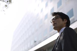 ビルの前で遠くを見るビジネス男性の写真素材 [FYI02972769]