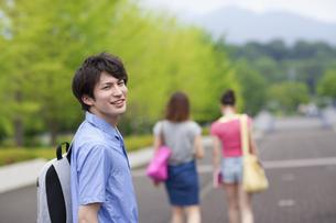 振り向いて微笑む男子学生の写真素材 [FYI02972776]