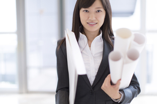 封筒と筒を持って立つビジネス女性の写真素材 [FYI02972782]