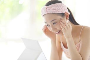 鏡の前で頬に両手をあてスキンケアをする女性の写真素材 [FYI02972783]