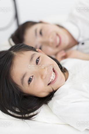 横になって笑う母と娘の写真素材 [FYI02972784]
