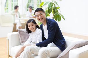 会話する祖父母とソファに掛けて笑顔の父と娘の写真素材 [FYI02972793]