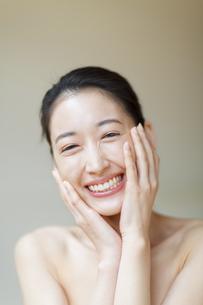 頬に両手を添えた笑顔の女性の写真素材 [FYI02972816]