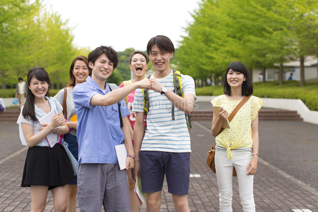 キャンパス内でこぶしを合わせる学生と仲間のスナップの写真素材 [FYI02972821]