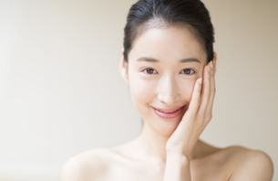 頬に片手を添えて微笑む女性の写真素材 [FYI02972825]