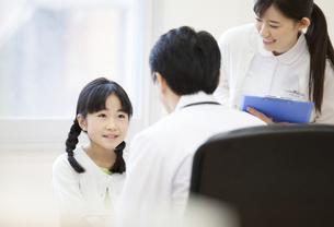 男性医師に問診されている女の子の写真素材 [FYI02972827]