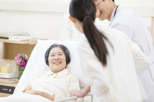 ベッドの患者を診察する男性医師と女性看護師の写真素材 [FYI02972832]