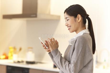 キッチンでスマートホンを持って微笑む女性の写真素材 [FYI02972837]