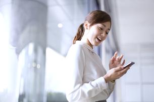 スマートフォンを見て笑うビジネス女性の写真素材 [FYI02972845]