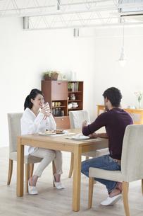 ダイニングテーブルで食事を楽しむ男性と女性の写真素材 [FYI02972848]