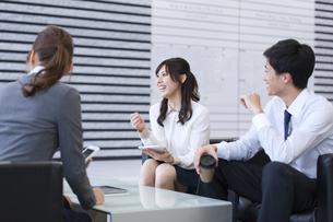 オフィスビルのロビーで座って会話するビジネス男女の写真素材 [FYI02972856]