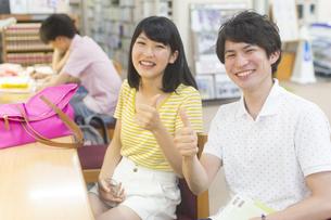 図書室でサインを出して笑う学生男女のポートレートの写真素材 [FYI02972858]