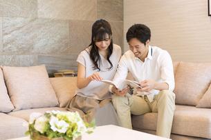 ソファーで本を見る夫婦の写真素材 [FYI02972862]