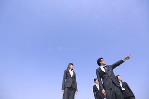 青空を背景に指をさす方向を見るビジネス男女の写真素材 [FYI02972878]