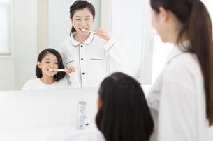 鏡に向かって歯磨きをする母と娘の写真素材 [FYI02972884]