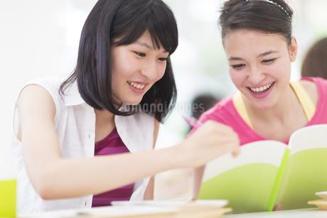 ノートを見て笑う2人の女子学生の写真素材 [FYI02972886]