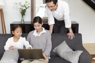 ソファーでノートパソコンを見る家族の写真素材 [FYI02972897]