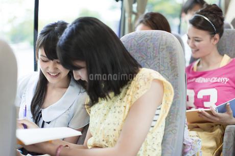 バスでノートをとる2人の女性と車中の様子の写真素材 [FYI02972901]