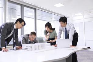会議室で建築模型を使って打ち合せをするビジネス男女の写真素材 [FYI02972927]