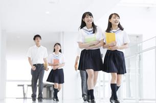 教材を持って笑いながら歩く学生たちの写真素材 [FYI02972940]