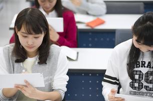 タブレットPCを持って授業を受ける女子生徒の写真素材 [FYI02972942]