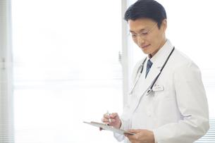 カルテを記入する男性医師の写真素材 [FYI02972944]