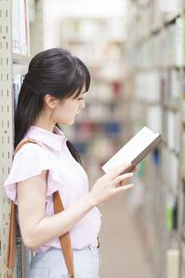 図書室で立って読書をする女子学生の写真素材 [FYI02972968]