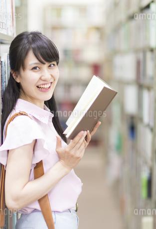 図書室で本を手に笑う女子学生のポートレートの写真素材 [FYI02972970]