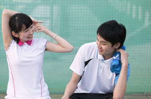テニスコートでリラックスをする男子学生と女子学生の写真素材 [FYI02972998]