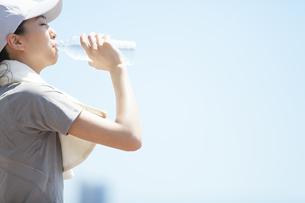 運動後にミネラルウォーターを飲む女性の横顔の写真素材 [FYI02973001]