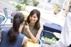 オープンカフェで食事をする女性2人の写真素材 [FYI02973010]