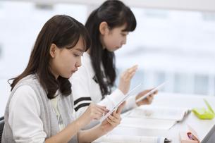 タブレットPCを持って授業を受ける女子生徒の写真素材 [FYI02973011]
