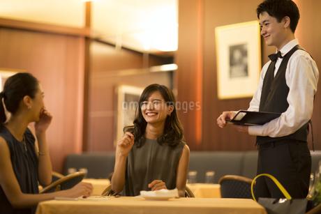 レストランで笑いながら店員と話す女性2人の写真素材 [FYI02973014]