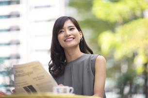 オープンカフェで新聞を持って微笑む女性の写真素材 [FYI02973021]