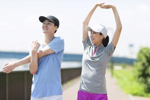 スポーツウエアを着てストレッチをする男性と女性の写真素材 [FYI02973023]