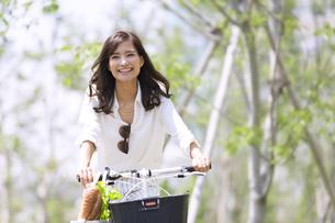 自転車で買い物をする女性の写真素材 [FYI02973030]